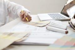 Projeto gráfico e amostras de folha e penas da cor em uma mesa Architectu Fotografia de Stock