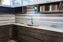 Projeto interior moderno da cozinha com os armários baixos marrons e os armários de parede brancos Fotos de Stock