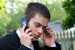 Prom Boy On Two Phones. Closeup of a teenage boy in prom attire with a cell phone to each ear, in an outdoor setting Royalty Free Stock Photo
