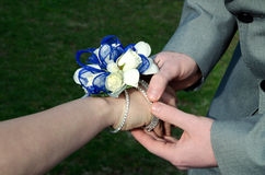 Prom Date. Teen boy putting a wrist corsage on his date for prom stock image