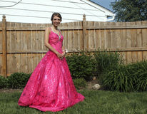 Prom Time. Girl poses outside in her beautiful pink prom dress stock photo
