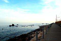 Promenad mellan järnvägsspår och vinkande det litet Adriatiskt havet med talrikt vaggar royaltyfri fotografi