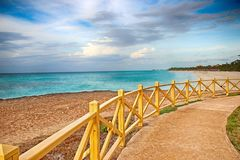 Promenade around the sea with a wooden railing and a view of the water. The clear turquoise sea of the Atlantic ocean on which are royalty free stock image