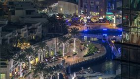 Promenade and canal in Dubai Marina with luxury skyscrapers and yachts around night timelapse, United Arab Emirates. Aerial top view with restaurants and cafes stock video footage