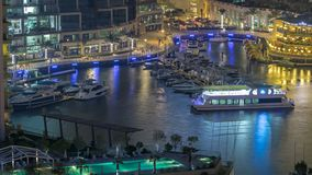 Promenade and canal in Dubai Marina with luxury skyscrapers and yachts around night timelapse, United Arab Emirates. Aerial top view with restaurants and cafes stock video