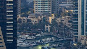 Promenade and canal in Dubai Marina with luxury skyscrapers and yachts around timelapse, United Arab Emirates. Aerial top view during sunset stock footage