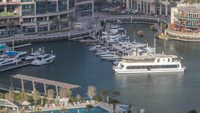 Promenade and canal in Dubai Marina with luxury skyscrapers and yachts around timelapse, United Arab Emirates. Aerial top view during sunset stock video