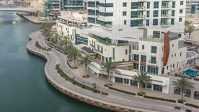 Promenade and canal in Dubai Marina with luxury skyscrapers and yachts around timelapse, United Arab Emirates. Aerial top view during sunset stock video footage