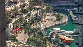 Promenade and canal in Dubai Marina timelapse with boats around, United Arab Emirates. Promenade and canal in Dubai Marina timelapse with boats and luxury stock video