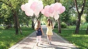Promenade d'enfants par le parc d'été avec des ballons deux petites filles tiennent beaucoup de ballons colorés La vue de banque de vidéos
