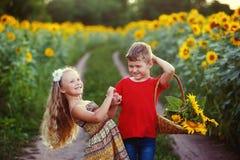 Promenade d'enfants près d'un champ des tournesols Le concept du children& x27 ; amitié de s Image libre de droits
