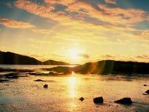 Promenade dans le coucher du soleil sur la plage Refléter de l'horizon sunsetting en eau de mer entre les roches image stock