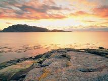 Promenade dans le coucher du soleil sur la plage Refléter de l'horizon sunsetting en eau de mer entre les roches photographie stock libre de droits