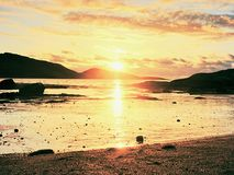 Promenade dans le coucher du soleil sur la plage Refléter de l'horizon sunsetting en eau de mer entre les roches photographie stock