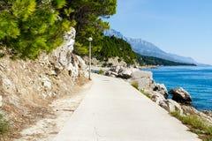 'promenade' de Brela en Makarska Rivier, montañas de Biokova en la parte posterior Imágenes de archivo libres de regalías