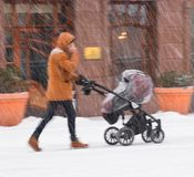 Promenade de famille avec l'enfant dans la poussette dans le jour neigeux de winetr images libres de droits