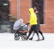 Promenade de famille avec l'enfant dans la poussette dans le jour neigeux de winetr photographie stock libre de droits
