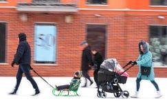 Promenade de famille avec l'enfant dans la poussette dans le jour neigeux de winetr photo stock