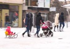 Promenade de famille avec l'enfant dans la poussette dans le jour neigeux de winetr image libre de droits