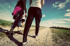 Promenade de famille dans la campagne un jour ensoleillé Perspective de jambes Regard de vintage Image libre de droits