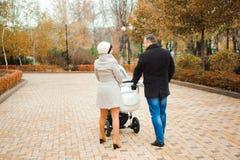 Promenade de famille en parc d'automne avec un landau Maman, papa et chéri images libres de droits