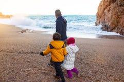 Promenade de famille par la mer, dans l'horaire d'hiver Passer le temps Photographie stock libre de droits