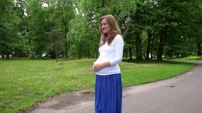 Promenade de femme enceinte de femme enceinte par le parc banque de vidéos