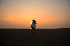 Promenade de fille de silhouette dans la mer Photographie stock libre de droits