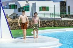 Promenade de l'adolescence de deux garçons à côté de la piscine Images stock