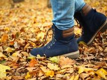 Promenade de l'enfant en parc, chemin complètement des feuilles, seulement jambes évidentes images stock