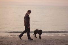Promenade de matin de l'homme un chien Images stock