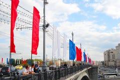 Promenade de personnes sur la rue décorée par des drapeaux Image libre de droits