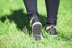 Promenade de pied avec l'étape sur l'herbe verte au jour ensoleillé, à la vue arrière aux jambes femelles avec des chaussures et  Photos libres de droits