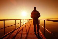 Promenade de silhouette d'homme sur la construction de quai au-dessus de la mer à Sun Matin fantastique images stock
