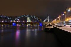 'promenade' del Daugava, puente del ferrocarril y puente iluminados de Vansu en Riga, Letonia imagen de archivo
