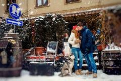 Promenade des ajouter heureux au chien de traîneau sibérien La belle femme principale rouge embrasse l'homme dans la joue près du Photographie stock