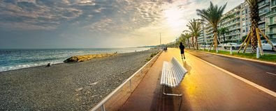 Promenade des Anglais in Nice at sunset. Cote d`Azur, French riviera, France. Panoramic view of beach and Promenade des Anglais at sunset in Nice. Cote d`Azur royalty free stock photos