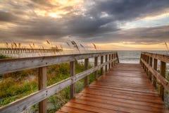 Promenade, die zu den Strand bei Sonnenaufgang führt lizenzfreie stockbilder