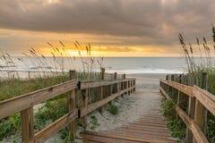 Promenade, die zu den Strand bei Sonnenaufgang f?hrt stockfotografie