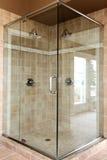 Promenade en verre neuve moderne dans la douche avec les tuiles beiges. image libre de droits