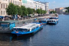 A promenade excursion boat станд at the embankment of the Fontanka River near Anichkov Bridge. RUSSIA, SAINT PETERSBURG - AUGUST 18, 2017: A stock photography