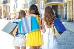 Promenade faisant des emplettes trois filles tenant des paniers et promenade autour Photographie stock