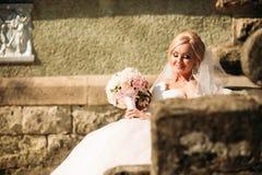 Promenade fantastique de jeune mariée près du palais Robe de mariage photo stock