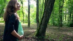 Promenade femelle dans l'expectative de sourire dans l'allée d'arbre de parc banque de vidéos