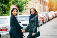 Promenade heureuse d'amie de deux filles par les rues de la ville Photographie stock libre de droits
