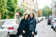 Promenade heureuse d'amie de deux filles par les rues de la ville Photo libre de droits