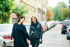 Promenade heureuse d'amie de deux filles par les rues de la ville Photos stock