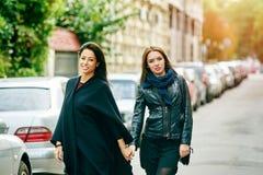 Promenade heureuse d'amie de deux filles par les rues de la ville Images stock