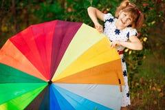 Promenade heureuse de fille d'enfant avec le parapluie multicolore sous la pluie image stock