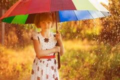Promenade heureuse de fille d'enfant avec le parapluie multicolore sous la pluie image libre de droits